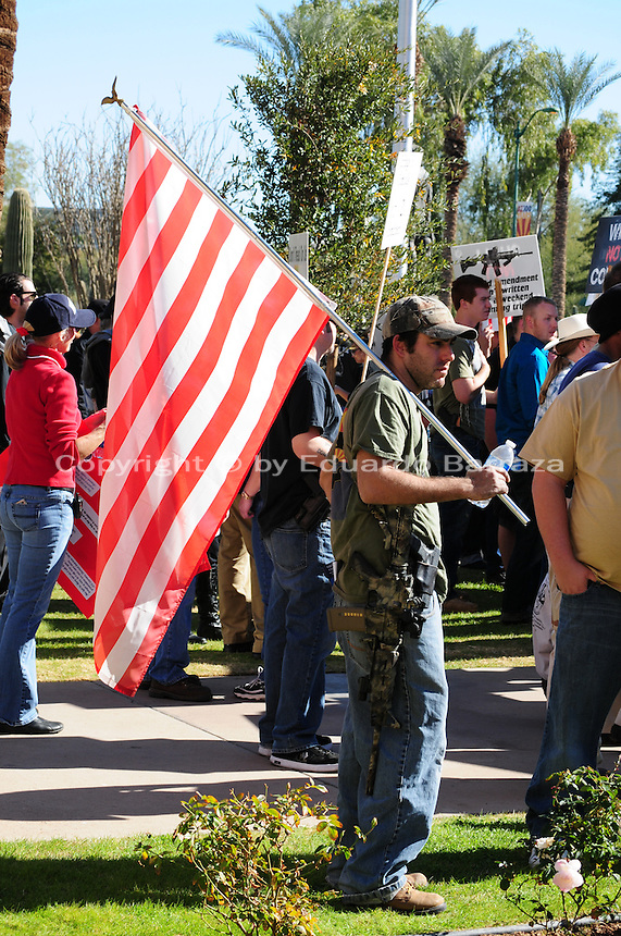"Phoenix, Arizona. January 19, 2013 - A protester displays an automated gun during Saturday's rally in Phoenix to oppose potential new laws that would limit access to guns and ammunition in the United States. As President Barack Obama proposed new gun regulations last week, gun owners demonstrated against it with national ""Guns Across America"" rallies to defend the Second Amendment. Dozens showed up at the Arizona State Capitol, many of them carrying weapons. Photo by Eduardo Barraza © 2013"