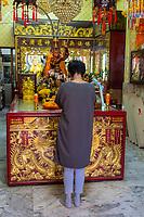 Bangkok, Thailand.  Woman Praying at Monkey King Shrine, Chinatown.