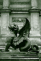 One of the two dragons of the fountain of Saint Michel in Paris, with its lion head, its open wings, and its rolled tail (black & white). Digitally Improved Photo.
