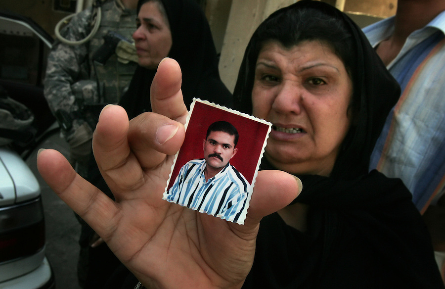A woman in the Sunni neighborhood of Ghazaliyah holds up the photograph of a next door neighbor executed at a checkpoint set up by a death-squad in the adjacent Shiite neighborhood of Shula. The scene took place on Wednesday August 16, 2006 during an operation by bolstered US and Iraqi forces with the aim of getting a handle on the extraordinary numbers of sectarian killings in Baghdad.