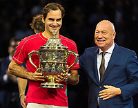 27th October 2019; St. Jakobshalle, Basel, Switzerland; ATP World Tour Tennis, Swiss Indoors Final; Roger Federer (SUI) receives the winners trophy from Tournament Director Roger Brennwald after winning the match against Alex de Minaur (AUS) - Editorial Use