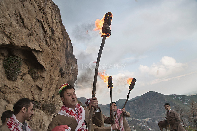 21/03/15 -- Akre, Iraq -- Young people from the Directorate of Culture in Akre set torches on fire and show them to the crowd, while people around them shoot guns to celebrate.