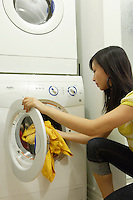 Montreal (Qc) CANADA, July 24, 2007 - Model Released photo- A young asian woman use high efficiency (HE) detergent to wash clothes in a front loader washing machine.<br /> <br /> Front-loading washing machines use:<br /> 40 to 60% less water<br /> 30 to 50% less energy<br /> 50 to 70% less detergent<br /> than top-loaders!<br /> <br /> Most of the energy used for washing clothes is consumed for heating the water. A typical top-loading washer uses about 40 gallons of water as compared to only 20 to 25 gallons in a front-loader.<br /> <br /> The gentle tumbling action of a front-loader is much easier on clothes than the twisting action they receive in a top-loader.<br /> <br /> The typical top-loader machine spins at about 600 rpm (revolutions per minute). Many front-loading machines spin faster -1000 rpm to1600 rpm. This forces more water out of the washing.<br /> <br /> Therefore, front loaders reduce drying time considerably because they spin much faster.<br /> <br /> In Europe, more than 90% of washing machines are front-loaders, compared with less than 5% in the U.S. <br /> <br /> photo : (c) images Distribution