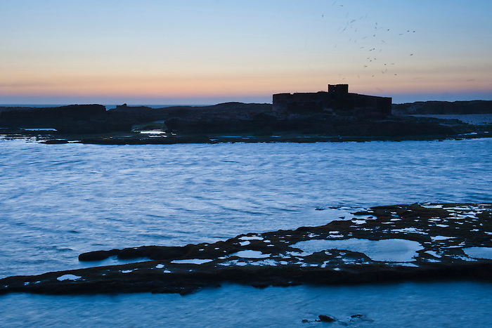 Photo of Mogador Island at sunet, Essaouira, formerly Mogador, Morocco, North Africa, Africa. This photo of Mogador Island at sunset was taken from Essaouira port. Mogador Island can only be visited with special permission due to being named a nature reserve.