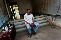 "A Cuban barber, waiting for customers, sits in the entrance to the apartment block in Bahía, a public housing suburb of Havana, Cuba, 11 February 2011. The Cuban economic transformation (after the revolution in 1959) has changed the housing status in Cuba from a consumer commodity into a social right. In 1970s, to overcome the serious housing shortage, the Cuban state took over the Soviet Union concept of social housing. Using prefabricated panel factories, donated to Cuba by Soviets, huge public housing complexes have risen in the outskirts of Cuban towns. Although these mass housing settlements provided habitation to many families, they often lack infrastructure, culture, shops, services and well-maintained public spaces. Many local residents have no feeling of belonging and inspite of living on a tropical island, they claim to be ""living in Siberia""."