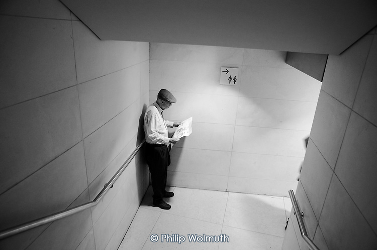 A man in a flat hat reading as he waits for his wife outside toilets in the British Museum.