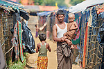 A man carries his child as he walks through the Jamtoli Refugee Camp near Cox's Bazar, Bangladesh. More than 600,000 Rohingya refugees have fled government-sanctioned violence in Myanmar for safety in this and other camps in Bangladesh.