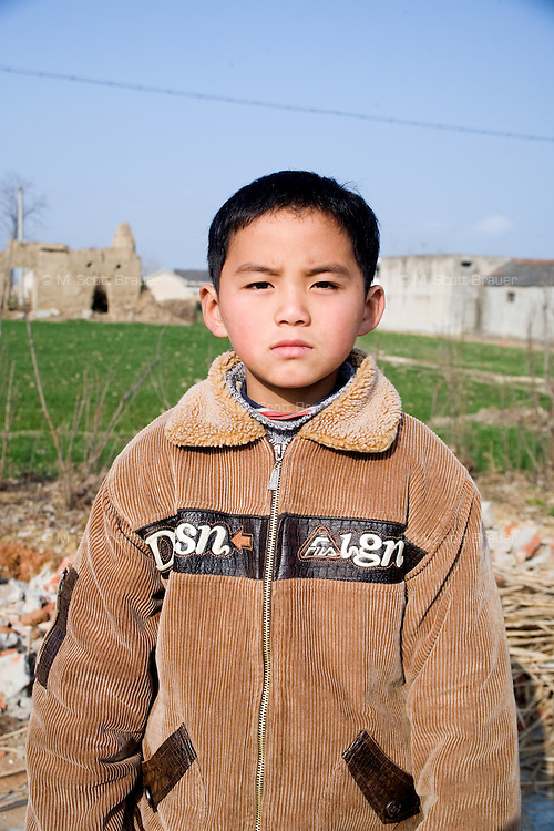 Zhao Shi stands near his family's house in Qingdun Village, Gangyun County, Jiangsu, China.  Zhao Shi has lived with his sister Zhao Min, 9, and grandparents Sun Zhan Xia (female) and Zhao Xia You (male) since 2007 when the children were orphaned in 2007. The children's father, Sun Zhan Xia's son, died of hepatitis in 2006 and their mother was forced to remarry and abandon the children in 2007.  Sun Zhan Xia and her husband are both over 60 and in bad health.  The couple owes approximately 40,000 RMB (about $5,300 USD) to pay for the medical treatment of their dead son, the children's father.  Due to their health situation and this enormous debt, the pair cannot afford to care for the children any longer, and the children are in danger of being placed in orphanages.  ..At the time of the picture, China's Amity Foundation charity, was investigating the family's situation in preparation to raise money to financially support these children and other orphans in similar situations.  With Amity's support, each orphan, aged 6-12, would receive approximately 1,400 RMB annually (about 200 USD) to pay for the cost of living. Amity works to keep children out of the institutional orphanages in China, preferring to provide monetary assistance that can help maintain a family environment for the orphans it helps.