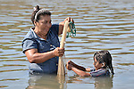 Guillermina Jarquin holds up her fishing net in a river near Santa Paula, a hot and isolated village in northwestern Nicaragua, while her daughter pulls out the fish she has caught.