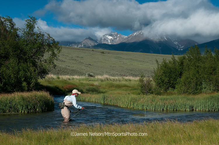An angler fly fishes for trout on Birch Creek, Idaho, with the Lemhi Mountains in the background.