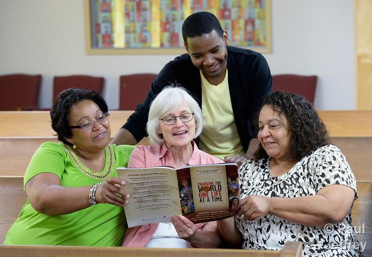 The Rev. Dr. Lyda Pierce (center), coordinator of Hispanic ministries for the Pacific Northwest Conference of the United Methodist Church, confers with members of the Palabra Viviente United Methodist Church in Everett, Washington. They are consulting the denomination's official program calendar. Kevin Sauceda is behind her. His mother, Zulma Tifre, a lay missioner assigned to a new church start, is on the left. Lourdes Tifre, a member of the conference immigration task force, is on the right.