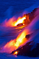 At sunset, glowing lava from Kilauea volcano flows into the ocean, Big Island of Hawai'i.