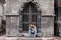 A boy sits in front of an old structure at Pashupati Nath temple in Kathmandu, Nepal