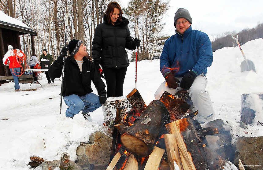 Staying warm by the fire while their kids play are, from left, Dave Lemieux and Kim Hardy of Atkinson and Tom Haslam of Stratham at the Winter Whiteout Festival at Stratham Hill Park in Stratham, N.H., N.H. Sunday, Jan. 30,  2011.  (Portsmouth Herald Photo Cheryl Senter)