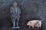 Worn lead models of rotund 19th century farmer and jaunty plump pig against mottled metal background