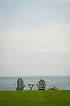 Two adirondack chairs facing Long Island Sound.
