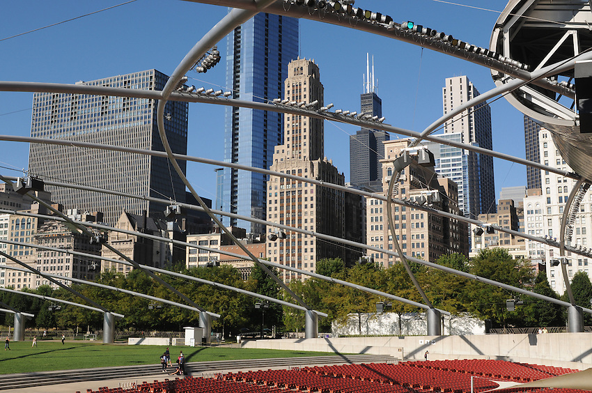 The Chicago skyline as seen through the web like lighting canopy of The Jay Pritzker Pavillion, one of architect Frank Gehry's career masterworks situated within Millenium Park.