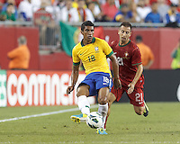 Brazil midfielder Paulinho (18) passes the ball as Portugal defender Joao Pereira (21) pressures. In an international friendly, Brazil (yellow/blue) defeated Portugal (red), 3-1, at Gillette Stadium on September 10, 2013.