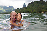 FRENCH POLYNESIA, Moorea. Lauren and her kids swimming by Opunohu Bay.