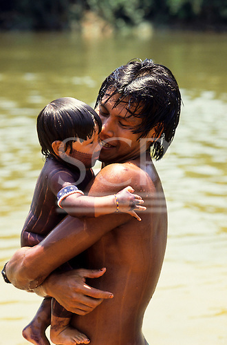 A-Ukre, Brazil. Bengoti, a Kayapo Indian man, with his child Gordon, named after Gordon Roddick of the Body Shop; Xingu.