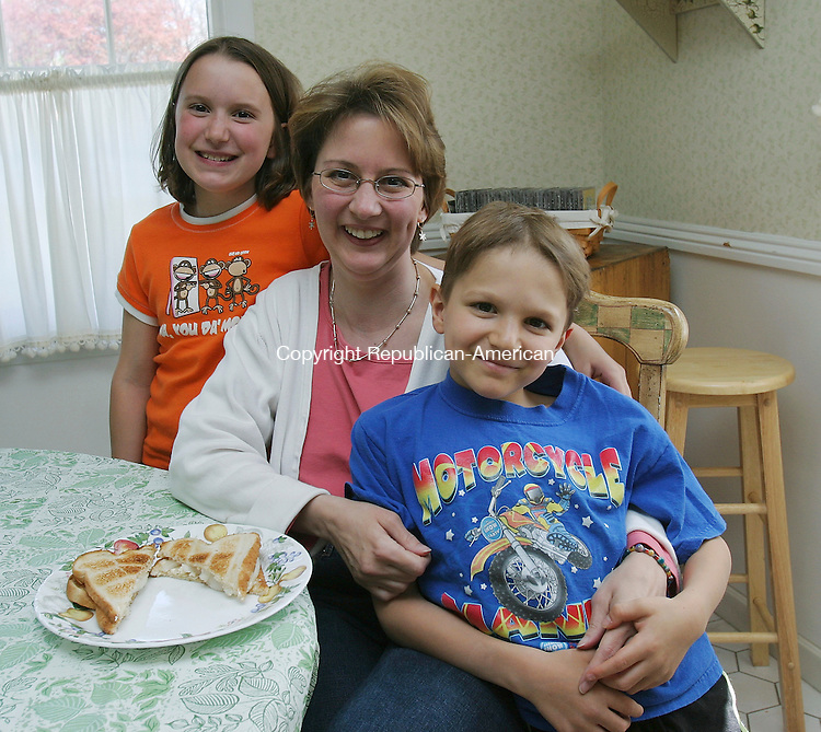WATERBURY, CT - 01 May 2005 -050105BZ02- From left- Elisa Cantito, 10, her mother Maria Cantito, and brother Andrew Cantito, 8, in their Waterbury home Sunday afternoon. Maria Cantito remembers making makes &quot;onion and butter&quot; sandwiches with her mother.<br />  Jamison C. Bazinet Photo