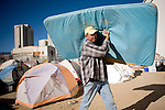 RENO, NV - OCTOBER 6:  Mike Moore carries a mattress out of a tent city for the homeless in downtown Reno, Nevada October 6, 2008. The City of Reno set up the tent city when existing shelters became overcrowded as Nevada struggles with one of the highest unemployment rates in the country. Today, Reno is evicting all male residents of the tent city, and housing them in a shelter in the nearby city of Sparks.(Photo by Max Whittaker/Getty Images)
