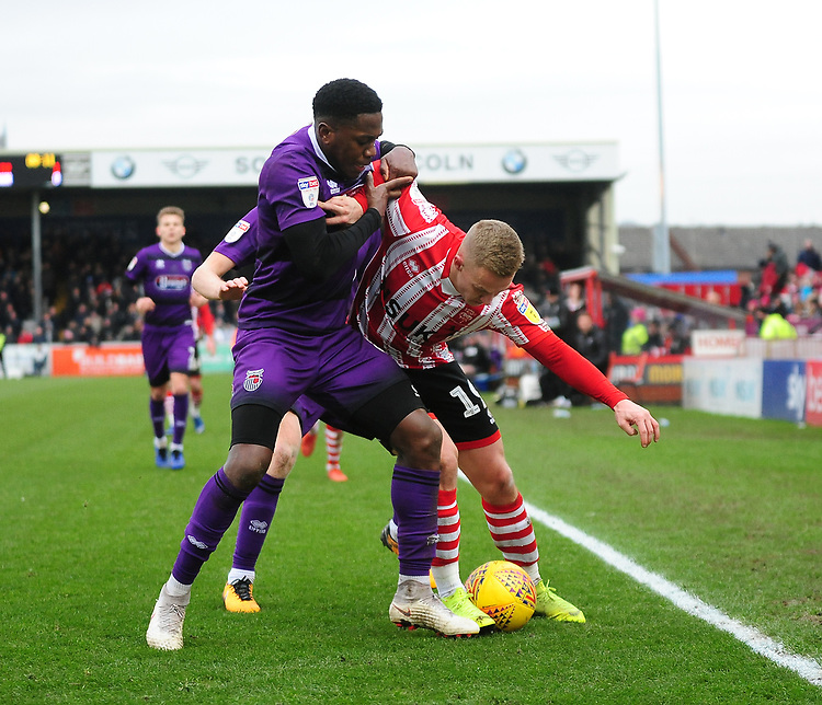Lincoln City's Danny Rowe battles with Grimsby Town's Mitch Rose<br /> <br /> Photographer Andrew Vaughan/CameraSport<br /> <br /> The EFL Sky Bet League Two - Lincoln City v Grimsby Town - Saturday 19 January 2019 - Sincil Bank - Lincoln<br /> <br /> World Copyright © 2019 CameraSport. All rights reserved. 43 Linden Ave. Countesthorpe. Leicester. England. LE8 5PG - Tel: +44 (0) 116 277 4147 - admin@camerasport.com - www.camerasport.com