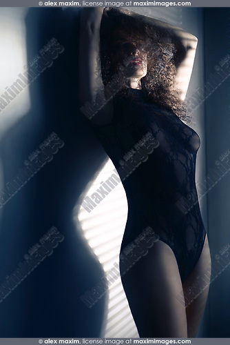 Sensual glamour portrait of a sexy beautiful woman with long corly hair covering her face wearing a black lacy bodysuit standing in dim window light