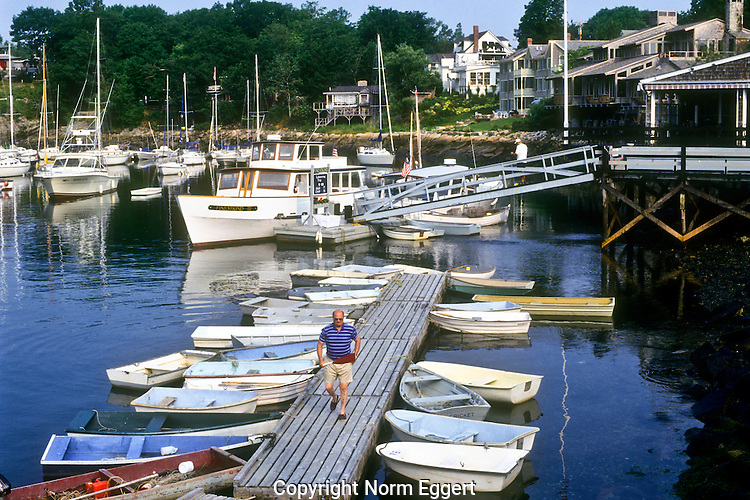 Man walks down the dock to his dinghy at Ogunquit Harbor