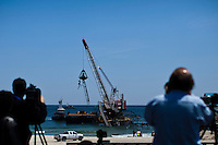 People take pictures while a crane works to remove remnants of the Jet Star roller coaster that had been left in the ocean after Superstorm Sandy hit Seaside Heights last year, in New Jersey  May 14, 2013, Photo by Eduardo Munoz Alvarez / VIEWpress.