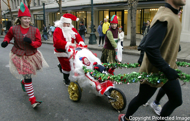 12/12/04 jinglebelldash13 news.Elves and Santa  follow joggers dressed as raindeer push a jogging stroller decked out as a sledge down 5th Avenue during the 20th annual Jingle Bell Run. Over 10,000 runners and walkers showed up to raise funds to support research, programs and services for the Arthritis Fondation. Jim Bryant/P.I. Photo