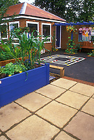 Children's garden at elementary school with raised beds, vines, patio, blacktop and games, plants