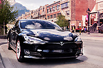 Black 2017 Tesla Model S luxury electric car parked on a city street in Banff, Alberta, Canada.