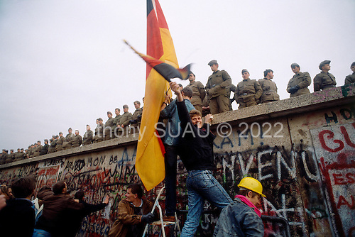 West Berlin, West Germany<br /> November 11, 1989<br /> <br /> Two German men hold German flags near the Berlin Wall. The East German government lifts travel and emigration restrictions to the West on November 9, 1989.