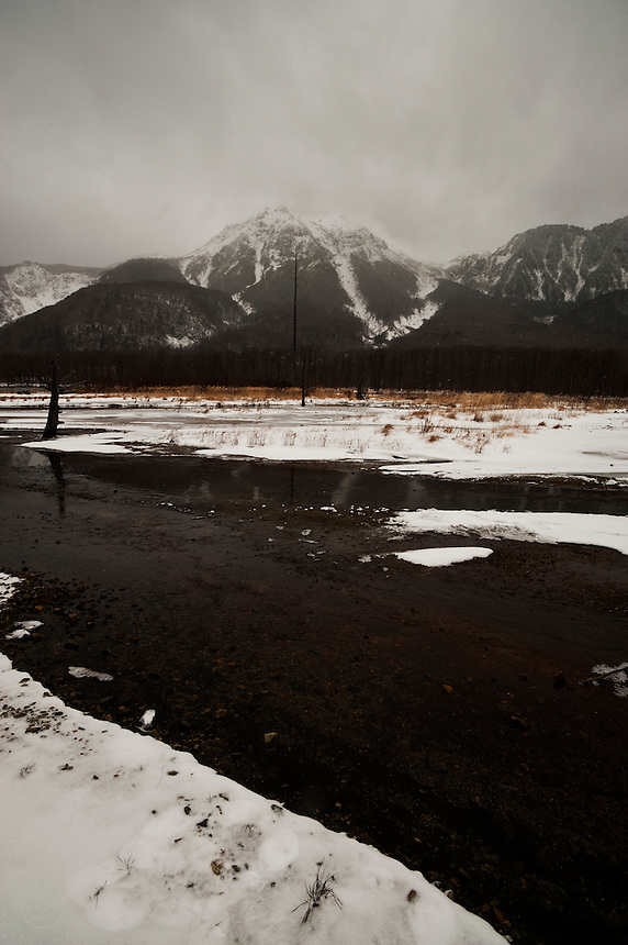 Mount Yake across Taisho-ike, nearly monochrome under light snow in winter, Kamikochi, Nagano, Japan.