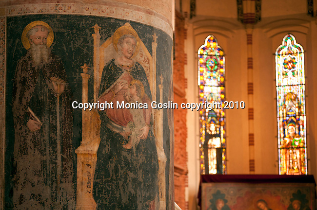 Detail of frescos on a column in the Basilica di Santa Anastasia in Verona, Italy with stained glass windows in the backgroun.