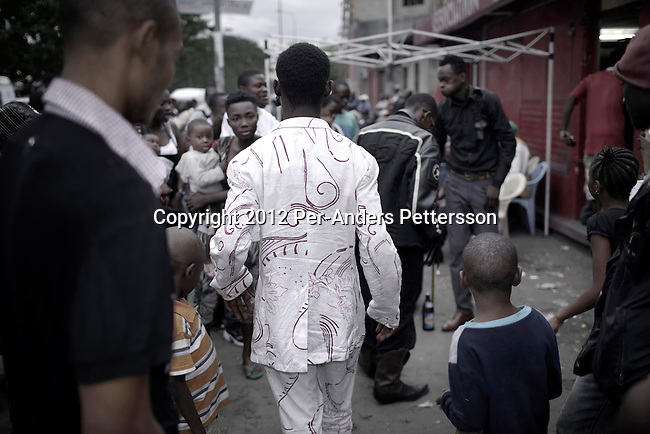 "KINSHASA, DEMOCRATIC REPUBLIC OF CONGO - FEBRUARY 10: A Sapeur shows his designer label clothes and on a busy street while paying his respect to Stervos Nyarcos, the founder of the kitendi religion, which means clothing in local language Lingala. Nyarcos was known as the leader of the Sape movement, at Gombe cemetery on February 10, 2012 in Kinshasa, DRC. The word Sapeur comes from SAPE, a French acronym for Société des Ambianceurs et Persons Élégants or Society of Revellers and Elegant People and it also means, to dress with elegance and style"". Most of the young Sapeurs are unemployed, poor and live in harsh conditions in Kinshasa,  a city of about 10 million people. For many of them being a Sapeur means they can escape their daily struggles and dress like fashionable Europeans. Many hustle to build up their expensive collections. Most Sapeurs could never afford to visit Paris, and usually relatives send or bring clothes back to Kinshasa. (Photo by Per-Anders Pettersson)"