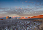 Idaho, North Central, Palouse, Moscow. Morning sun lights the hills of the Palouse under a setting moon and around a farm.
