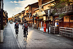 Cyclists on an empty Hanamikoji Dori street in Gion district in morning sunrise before all the shops and restaurants start opening. Hanami-koji, Gionmachi Minamigawa, Higashiyama Ward, Kyoto, Japan 2017.