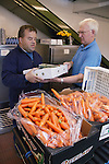 Man with learning disability at work at Brook Farm, Linby, carrying boxes of fresh vegetables. MR