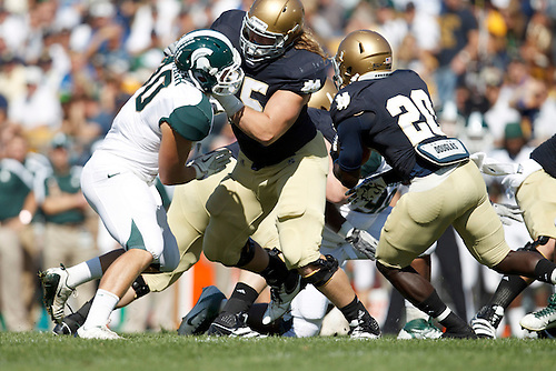Notre Dame offensive tackle Taylor Dever (#75) blocks Michigan State linebacker Max Bullough (#40) to open running lane for Notre Dame running back Cierre Wood (#20) in action during NCAA football game between Notre Dame and Michigan State.  The Notre Dame Fighting Irish defeated the Michigan State Spartans 31-13 in game at Notre Dame Stadium in South Bend, Indiana.