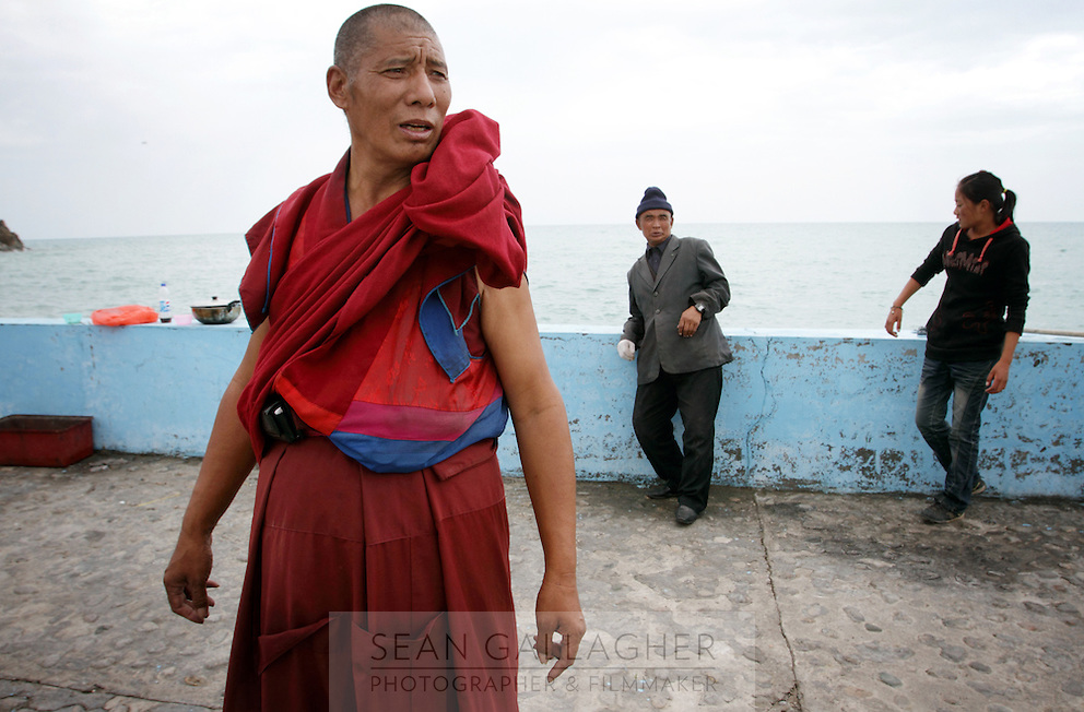A Tibetan monk near to Qinghai Lake. Qinghai Lake, China's largest inland body of water lies at over 3000m on the Qinghai-Tibetan Plateau. The lake has been shrinking in recent decades, as a result of increased water-usage for local agriculture. Qinghai Province. China. 2010
