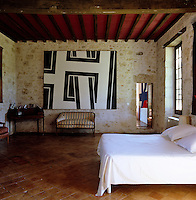 A large black and white abstract painting by Pierre Clerk hangs on the stone wall of the bedroom