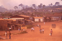 Daily life at Novo Repatimento village crossed by Transamazonica road - hotel sign in foreground - Amazon rainforest burning in background.