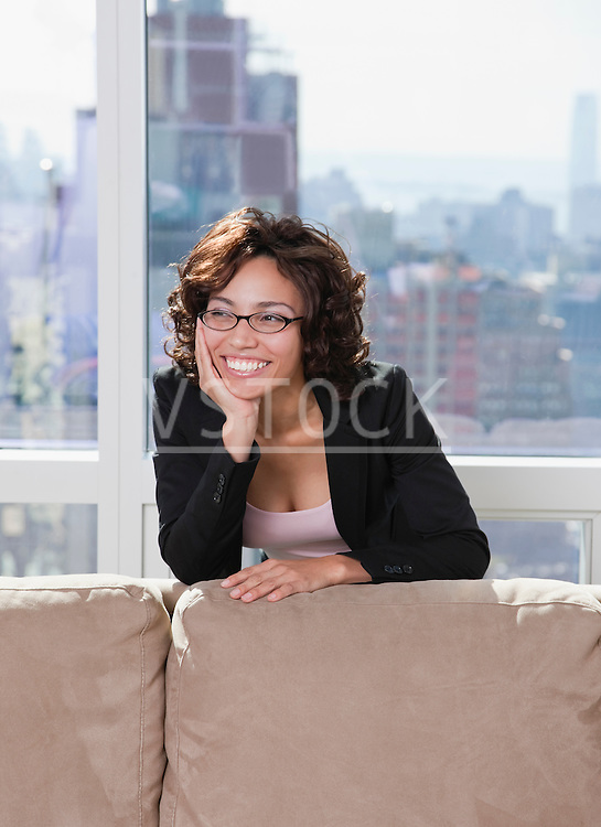 USA, New York State, New York City, business woman relaxing behind sofa