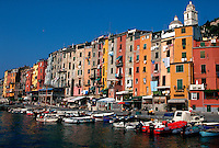 Portovenere, Italy. Long view of colorful buildings, cafes, and boats in the harbor.