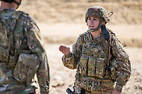 Young woman soldier in desert wearing US Army OCP Multicam uniform, using radio, giving male soldier directions and orders