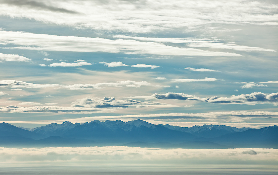 Discovery Bay is seen among patchy clouds and cool blues.  Mount Deception is in the distance as seen from Mt. Erie.