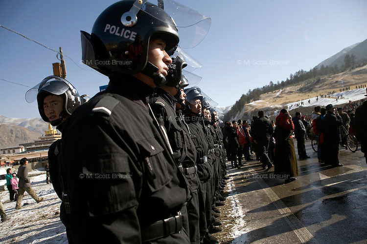 Police keep watch over crowds of Xiahe, Gansu, China.  The city, home to the Labrang Monastery, is an important religious site outside of Tibet for Tibetan Buddhists. Since uprisings in 2008, the city has been under military and police surveillance.