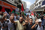 """Palestinian Hamas supporters wave national flags while holding pictures of Sheik Raed Salah, the leader of the Islamic Movement in Jerusalem, during a protest to condemn the desecration of Al-Aqsa Mosque in Jerusalem by Jewish extremists early morning in Gaza City, Wednesday, Sept. 4, 2013. Arabic reads, """"Freedom for the lion of Al-Aqsa"""". Members of Jewish groups entered the Al-Aqsa Mosque under the protection of Israeli police on Wednesday. They prayed in front of the mosque before clashes broke out with Palestinian Muslims. Photo by Ashraf Amra"""